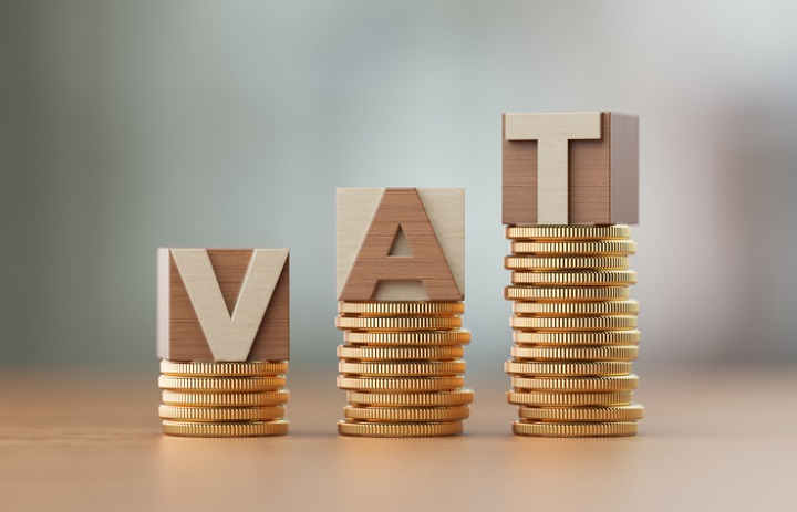 Cube blocks made of wood material are standing on coin towers to form VAT text over defocused background. Horizontal composition with copy space. Great use for finance concepts.